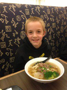 My adventurous son with his pork rib noodle bowl (March 2016).