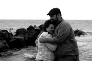 Michelle and her husband at the beach on Lake Erie taking engagement pictures