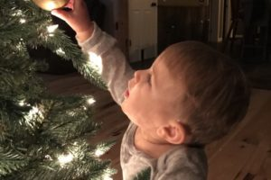 Child reaching for Christmas ornaments on Christmas tree