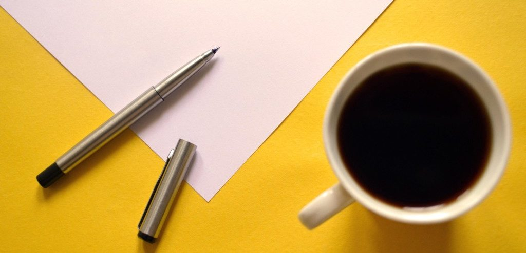 Paper and pen on yellow table with black coffee on the side