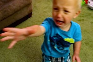 Toddler cries reaching for object.
