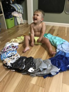 Toddler in cloth diaper surrounded by a ring of assorted cloth diapers