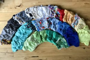 Set of one-size, all-in-one cloth diapers arranged in a rainbow pattern