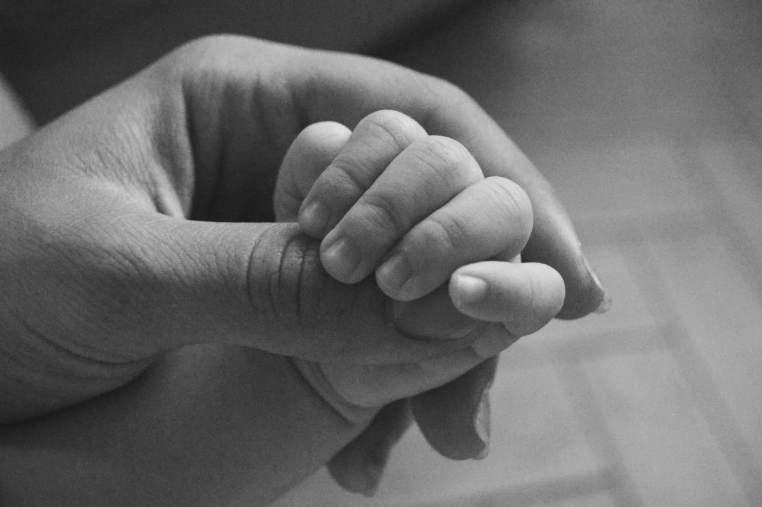 Black and white photo of baby's hand in mother's
