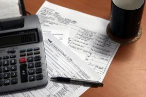 Tax documents, calculator, and coffee mug on a desk.