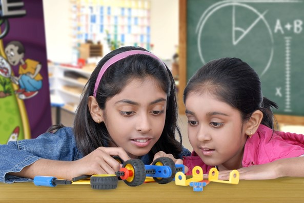 two young girls playing with mechanical blocks