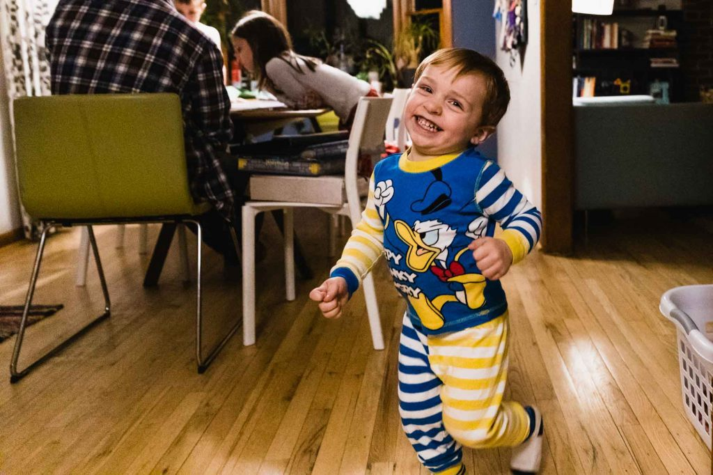 toddler in pajamas laughing and running through house while family sits at the table in the background