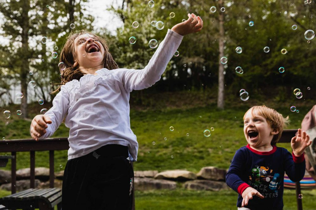 kids are playing with bubbles outside