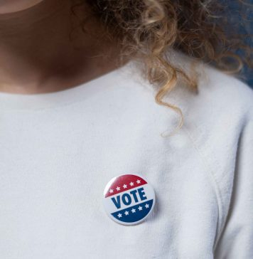 vote button on woman wearing white sweatshirt, with curly hair