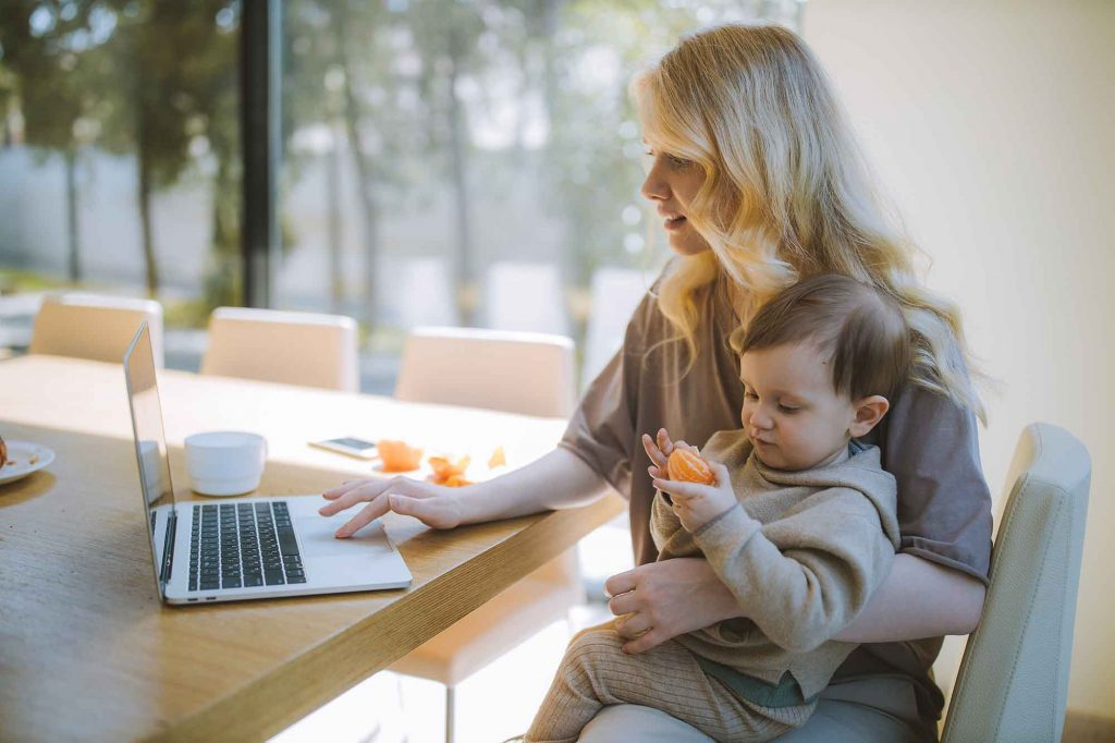 mom sitting at kitchen table with baby on her lap while she does research on the computer laptop