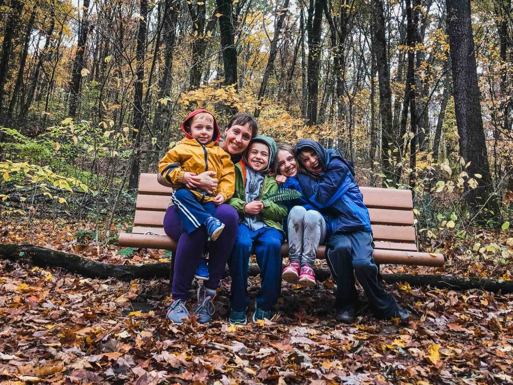 mom and four kids cuddled together outside on a bench smiling