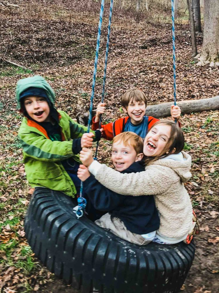 kids swinging on a tire swing outside in nature in the cold weather