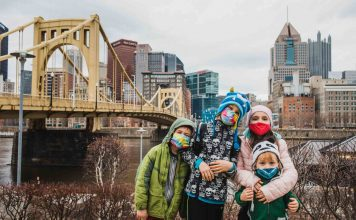kids wearing masks standing in front of the city of pittsburgh and the roberto clemente bridge